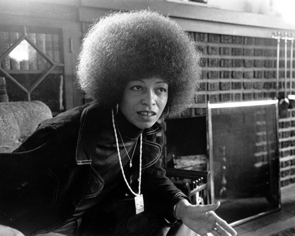 Black militant Angela Davis is seen at home in East Oakland, Calif. on Sept. 9, 1974. She wears two chains representing her commitment to struggle. One is gold, with the hammer and sickle of the Communist Party. The other is ivory with a dragon, ancient symbol of strength and harbinger of revolution. (AP Photo/stf)