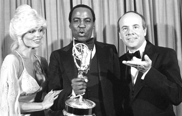 "FILE - In this Sept. 10, 1979 file photo, Robert Guillaume, center, accepts his Emmy Award for best supporting actor in a comedy-variety or music series for his role in ""Soap"" from Tim Conway, right, and Loni Anderson at the 31st Emmy Awards in Los Angeles. Guillaume, who won Emmy Awards for his roles on ""Soap"" and ""Benson,"" died Tuesday, Oct. 24, 2017 in Los Angeles at age 89. Guillaume's widow Donna Brown Guillaume says he had been battling prostate cancer. (AP Photo/Reed Saxon, File)"